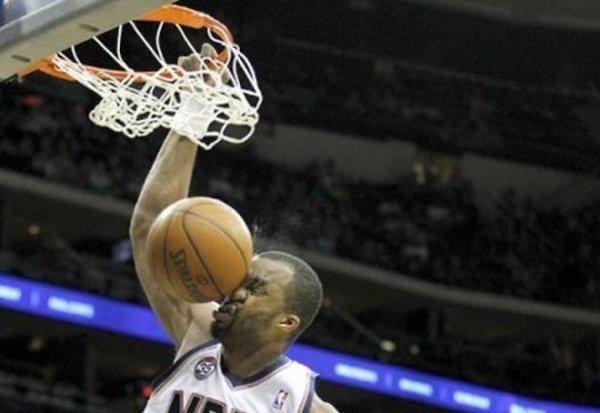 Un grandullón estrellándose una pelota de baloncesto en la cara al hacer un mate.
